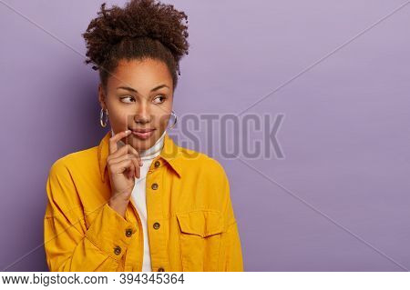 Horizontal Shot Of Attractive Curly Young Lady Plans Her Vacation, Keeps Hand Near Lips, Looks Aside