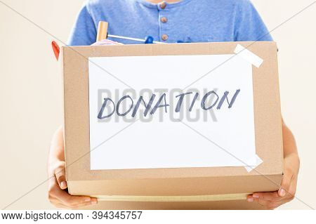 Donation Concept. Volunteer Hands Holding Donate Box With Clothes, Books And Toys For Charity