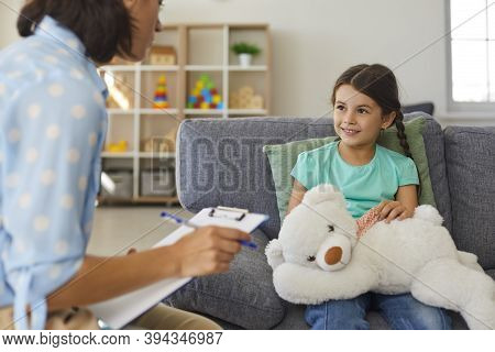 Cute Little Girl Talking To Child Psychologist During Therapy Session In Cozy Modern Office