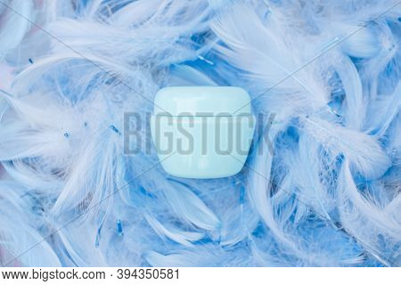 Spa Cosmetic Product, Cream Jar, Branding Mock Up, Top View On Blue Feathers Background. Flat Lay