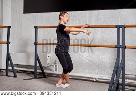 Beautiful Slender Guy In Sports Clothes Dancing Ballet In The Classroom.