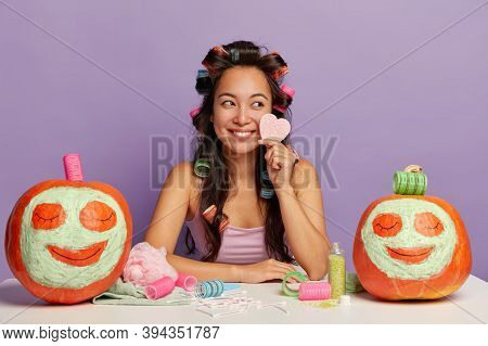 Smiling Beautiful Multiracial Female Uses Makeup Products, Holds Cosmetic Sponge For Face Care, Has