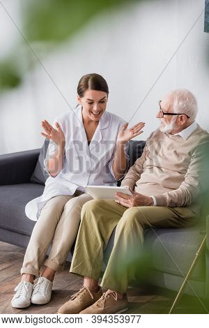 Geriatric Nurse Sitting With Open Arms Near Elderly Man And Digital Tablet On Blurred Foreground