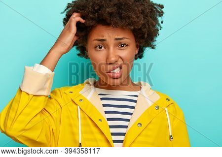 Puzzled Curly Woman Scratches Head, Smirks Face And Looks Confusingly At Camera, Faces Troublesome S