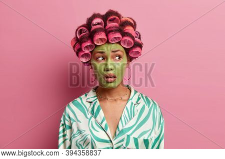 Beautiful Ethnic Woman Has Worried Expression, Looks Away, Applies Green Beauty Mask For Reducing Fi