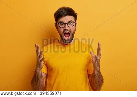 Waist Up Shot Of Furious Man Shouts And Gestures With Anger, Keeps Mouth Opened, Being Crossed With