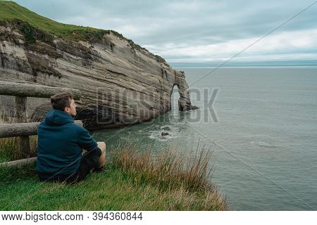 Young Caucasian Man Sitting On Top Of The Cliff And Looking At Cape Farewell Rock Formation. New Zea