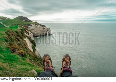Pair Of Traveler Shoes At Top Of Cliffs In Cape Farewell, New Zealand Coastline.