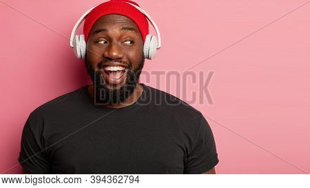 Photo Of Handsome Bearded Man Has Toothy Broad Smile, Looks Aside, Enjoys Favourite Melody In Headph