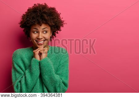 Positive Afro American Woman Looks With Gently Smile Aside, Remembers Pleasant Moment, Keeps Hands P