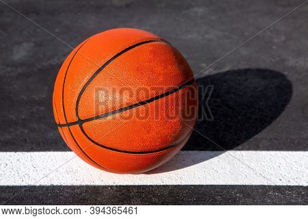 Orange Striped Basketball Ball Stands On The White Line Marking The Playing Field With Asphalt Tarma