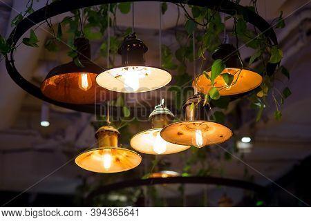 Several Round Pendant Retro Loft Style Lanterns With Edison Bulbs Shine With Warm Light In Interior