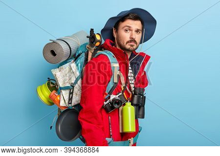 Photo Of Active Handsome Man With Mustache And Bristle, Carries Tourist Rucksack On Back, Walks In F