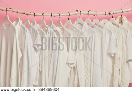 White Solid Clothes Hanging In One Row On Wooden Racks Against Pink Background. Big Choice For Women