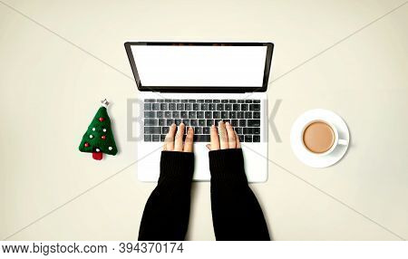 Person Using A Laptop Computer With A Christmas Tree Cushion And A Cup Of Coffee From Above
