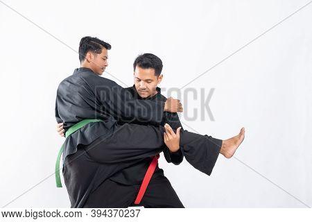 Two Fighters In Black Pencak Silat Uniform Fight In Locks And Slams