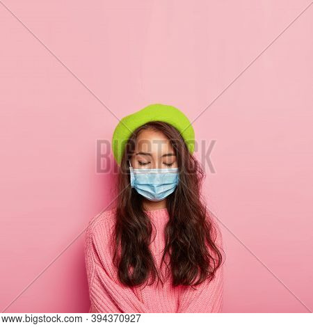 Vertical Image Of Calm Ill Woman Covers Nose And Mouth With Medical Mask, Has Infectious Disease, We