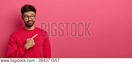 Curious Unshaven Man With Cheerful Smile, Introduces New Interesting Promo, Points Right And Invites