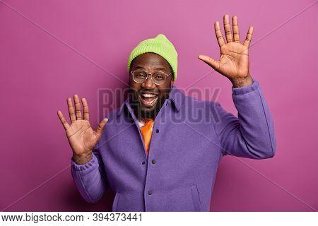 Joyful Black Man Raises Palms With Happiness, Dances Happily, Enjoys Party, Feels Carefree, Enjoys S
