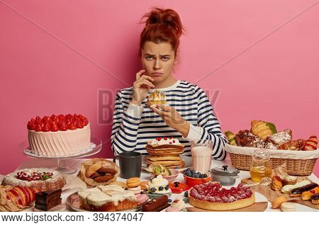 Dissatisfied Redhead Girl In Striped Jumper Has Sweet Food Addiction, Fed Up With Diets, Eats Variou