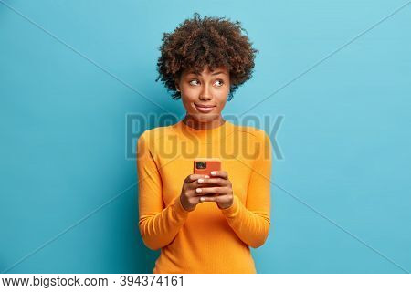 Pensive Delighted Young African American Woman Holds Mobile Phone And Types Message Uses Modern Tech