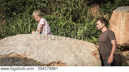 Sad Serious Boy Bored Climbed Hiding On Stone. Loving Father Wants To Help. Family Relations Closene