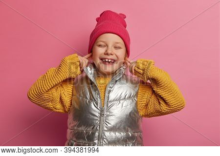 Smiling Merry Little Child Plugs Ears With Fore Fingers, Doesnt Want To Hear Noisy Neighbours, Wears