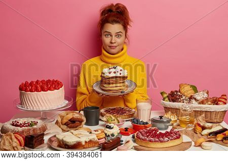 Surprised Redhead Woman Holds Plate With Delicious Pancakes And Berries, Being Impatient To Taste Ho