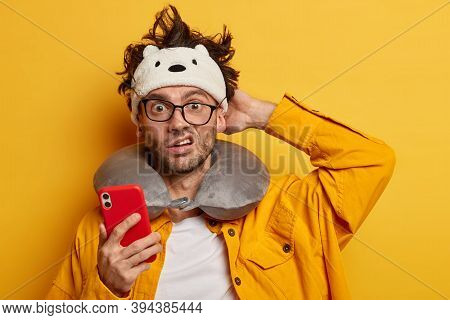 Indignant Puzzled European Man Scratches Head, Reads News Online Via Mobile Phone, Prepares For Trav