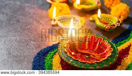 Close Up Clay Lit Light A Fire Already On Diya Or Oil Lamp With Flowers On Concrete Background, Deco