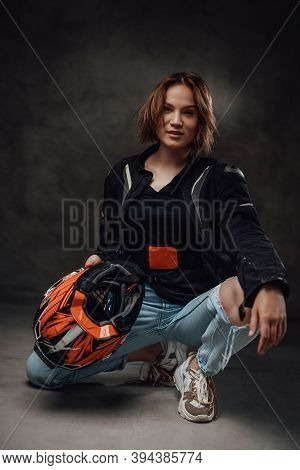 Cheerful Female Motorcyclist With Short Haircut Dressed In Black Jacket With Ragged Jeans Poses In D