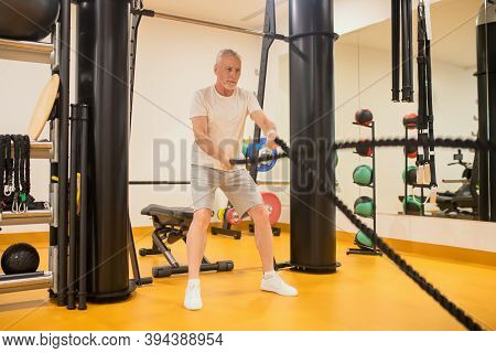A Man In Sportswear Pulling The Ropes In Gym
