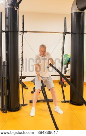 Grey-haired Man In Sportswear Pulling The Ropes In Gym