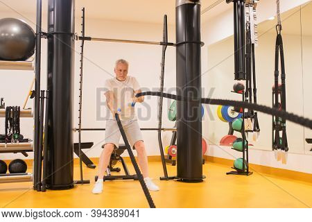 Marure Man In Sportswear Pulling The Ropes In Gym