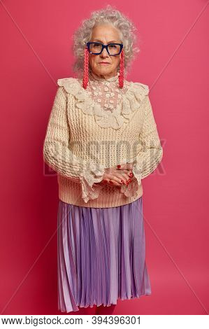 Well Groomed Beautiful Wrinkled Elderly Woman Looks Seriously At Camera, Keeps Hands Together, Wears