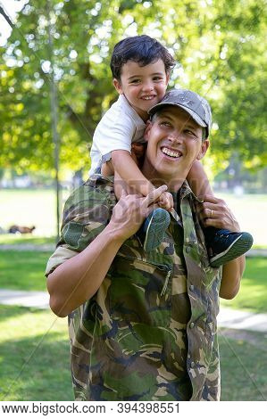 Caucasian Dad Holding Son On Neck And Smiling. Happy Cute Boy Hugging Father In Military Uniform. Ad