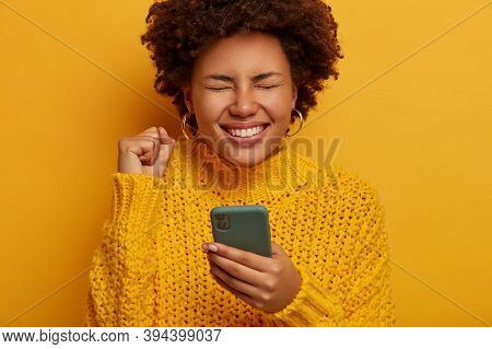 Cropped Shot Of Ecstatic Dark Skinned Woman Clenches Fist And Rejoices Victory, Holds Mobile Phone,