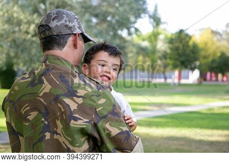 Back View Of Caucasian Man Holding Kid And Wearing Army Uniform. Cheerful Little Boy Sitting On Fath