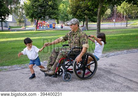 Disabled Veteran Of War Walking With Children In Park And Smiling. Cute Little Boy Holding Father Ha