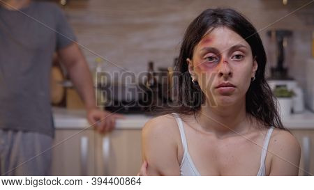 Portrait Of Hopeless Beaten Woman Sitting On The Chair In The Kitchen. Traumatised Abused Terrified