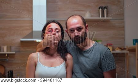 Scared Victim Of Domestic Violence Trembling Near Man. Violent Aggressive Man Abusing Injuring Terri