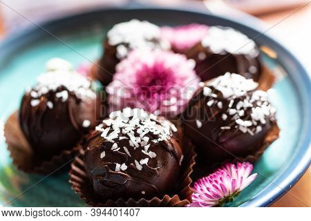Side View, Sweet Chocolate Balls Filled With Coconut And Coconut Flakes And Garnished With Pink Flow