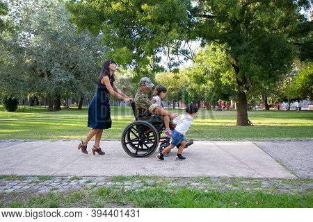 Cheerful Family Walking With Disabled Father In Military Uniform. Pretty Mom Pushing Wheelchair. Cut