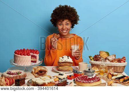 Glad Smiling Woman With Afro Curly Hairdo Eats Tasty Pastry With Milk, Has Good Mood To Eat Deliciou