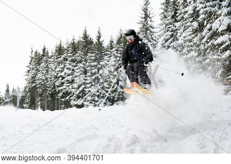 Male Skier In Ski Suit And Goggles Sliding Down Snow-covered Slopes On Skis With Snowy Pine Trees On