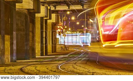 Public Transportation In A City. Tram Leaving The Station, Traffic Lights, People, Street, Houses, O
