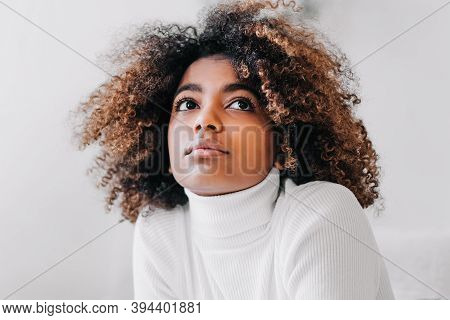 Nice Model With Perfect Dark Skin And Trendy Short Brown Kinky Hair Looking Upwards Against White St