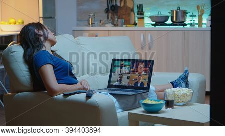 Lady In Pajamas Sitting On Sofa Having Online Meeting With Project Partners. Remote Worker Discussin