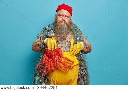 Dejected Bearded Stout Man Mariner Being In Bad Mood, Holds Red Octopus And Wears Overalls. Offended