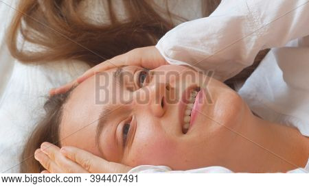 Calm Young Woman Sleeping Well In Comfortable Cozy Bed On White Soft Pillows Linen And Waking Up In